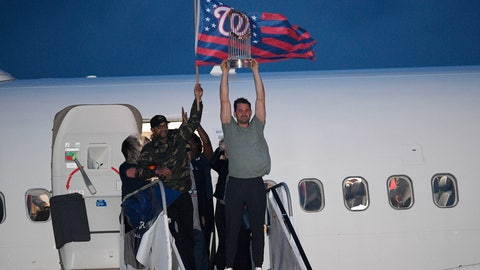 <p>               Washington Nationals manager Dave Martinez, left, waves a flag and Ryan Zimmerman, right, hoists the World Series trophy as the baseball team arrives at Dulles Airport, Thursday, Oct. 31, 2019, in Chantilly, Va. (AP Photo/Nick Wass)             </p>
