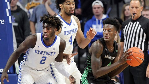 <p>               Utah Valley's Emmanuel Olojakpoke, right, looks for an opening on Kentucky's Kahlil Whitney (2) and Nick Richards (4) during the first half of an NCAA college basketball game in Lexington, Ky., Monday, Nov. 18, 2019. (AP Photo/James Crisp)             </p>