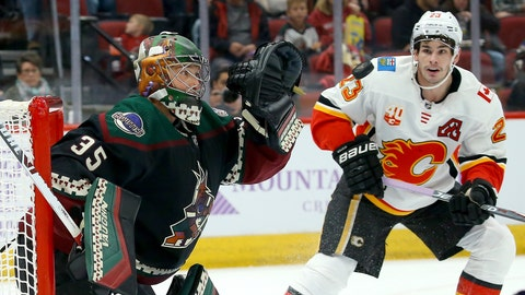 <p>               Arizona Coyotes goaltender Darcy Kuemper (35) reaches out to make a glove save on a shot as Calgary Flames center Sean Monahan (23) looks on during the first period of an NHL hockey game, Saturday, Nov. 16, 2019, in Glendale, Ariz. (AP Photo/Ross D. Franklin)             </p>