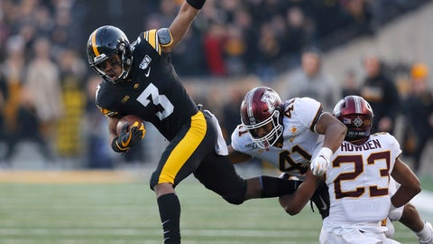<p>               Iowa wide receiver Tyrone Tracy, left, runs for a first down and tries to elude a tackle by Minnesota linebacker Thomas Barber, center, and defensive back Jordan Howden, right, during the first half of an NCAA college football game, Saturday, Nov. 16, 2019, in Iowa City, Iowa. (AP Photo/Matthew Putney)             </p>