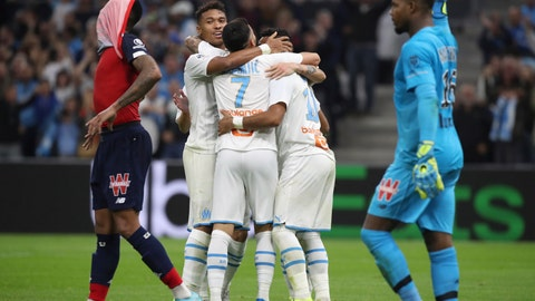 <p>               Marseille players celebrate after Lille's Gabriel scored an own goal during the French League One soccer match between Marseille and Lille at the Velodrome stadium in Marseille, southern France, Saturday, Nov. 2, 2019. (AP Photo/Daniel Cole)             </p>