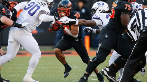 <p>               Oklahoma State running back Chuba Hubbard (30) breaks through the TCU line past defensive tackle Ross Blacklock (90) and defensive end Ochaun Mathis (32) for a long touchdown run in the second half of an NCAA college football game in Stillwater, Okla., Saturday, Nov. 2, 2019. (AP Photo/Sue Ogrocki)             </p>