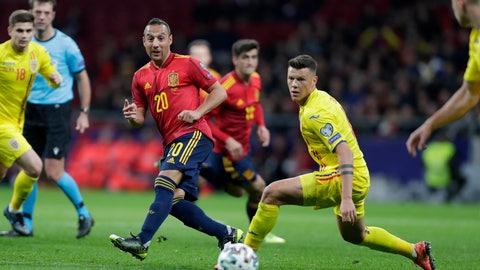 <p>               Spain's Santi Carzola, center, send the ball past Romania's Razvan Rus during the Euro 2020 group F qualifying soccer match between Spain and Romania at the Metropolitano stadium in Madrid, Monday, Nov. 18, 2019. (AP Photo/Manu Fernandez)             </p>