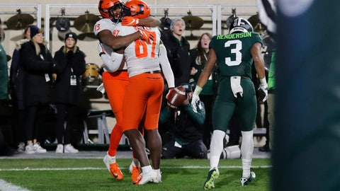 <p>               Illinois wide receiver Caleb Reams (13) hugs teammate tight end Daniel Barker (87) after Baker scored in the closing seconds to defeat Michigan State during the second half of an NCAA college football game, Saturday, Nov. 9, 2019, in East Lansing, Mich. (AP Photo/Carlos Osorio)             </p>