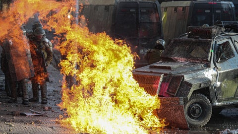 <p>               A petrol bomb explodes in front of a police vehicle during clashes with anti-government demonstrators in Santiago, Chile, Tuesday, Nov. 12, 2019. Students in Chile began protesting nearly a month ago over a subway fare hike. The demonstrations have morphed into a massive protest movement demanding improvements in basic services and benefits, including pensions, health, and education. (AP Photo/Esteban Felix)             </p>