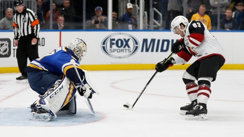 Arizona Coyotes' Conor Garland, right, scores the game-winning goal past St. Louis Blues goaltender Jordan Binnington during a shootout of an NHL hockey game Tuesday, Nov. 12, 2019, in St. Louis. The Coyotes won 3-2. (AP Photo/Jeff Roberson)