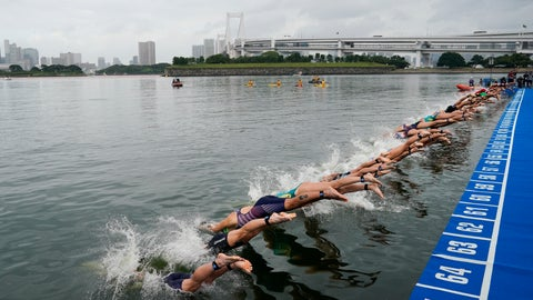 """<p>               FILE - In this Aug. 15, 2019, file photo, athletes dive into the water at the start line during a women's triathlon test event at Odaiba Marine Park, a venue for marathon swimming and triathlon at the Tokyo 2020 Olympics, in Tokyo. The IOC moved next year's Tokyo Olympic marathons and race walks out of the Japanese capital to avoid the stifling heat and humidity. Some swimmers and an 11,000-member coaching body want similar treatment: find an alternative to the distance-swimming venue in Tokyo Bay known as the """"Odaiba Marine Park.""""(AP Photo/Jae C. Hong, File)             </p>"""