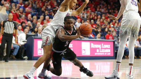 <p>               Omaha guard KJ Robinson (5) passes the ball in between Arizona guard Jemarl Baker Jr. and Christian Koloko (35) in the first half during an NCAA college basketball game, Wednesday, Dec. 11, 2019, in Tucson, Ariz. (AP Photo/Rick Scuteri)             </p>