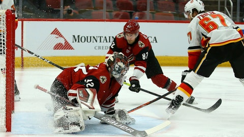 <p>               Calgary Flames right wing Michael Frolik (67) gets the puck past Arizona Coyotes goaltender Antti Raanta (32) and Coyotes defenseman Jordan Oesterle (82) for a goal during the first period of an NHL hockey game Tuesday, Dec. 10, 2019 in Glendale, Ariz. (AP Photo/Ross D. Franklin)             </p>