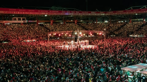 <p>               Many thousands of people take part in the Christmas carol singing event at the Alte Forsterei stadium of the German first division team of 1.FC Union Berlin, in Berlin, Germany, Monday, Dec. 23, 2019. The mass public event draws thousands of people to celebrate the festive season with the singing of Christmas carols. (Paul Zinken/dpa via AP)             </p>
