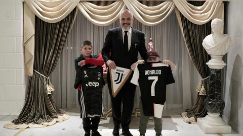 <p>               Albanian Prime Minister Edi Rama, center, poses with Aurel Lala and Alesio Cakoni, in Rome on Friday, Dec. 6, 2019. The two Albanian children were injured when they escaped their collapsing flat jolted from the Nov. 26 6.4-magnitude earthquake, that killed 51 persons and injured more than 3,000 others. They lost each two family members but their dream came true when Rama took them to Rome, Italy to meet with their sport idols Ronaldo and Buffon. (Albanian Prime Minister Office via AP)             </p>