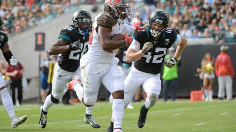 <p>               Tampa Bay Buccaneers running back Peyton Barber, center, runs for yardage past Jacksonville Jaguars free safety Jarrod Wilson (26) and defensive back Andrew Wingard (42) during the first half of an NFL football game, Sunday, Dec. 1, 2019, in Jacksonville, Fla. (AP Photo/Phelan M. Ebenhack)             </p>