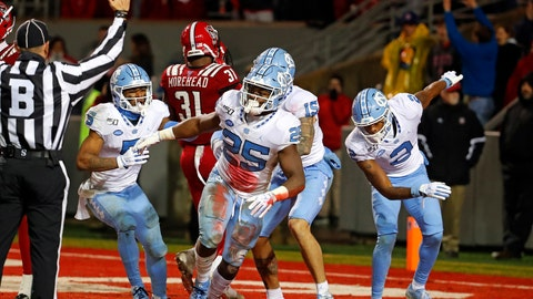 <p>               North Carolina's Javonte Williams (25) celebrates a touchdown against North Carolina State with teammates during the second half of an NCAA college football game in Raleigh, N.C., Saturday, Nov. 30, 2019. (AP Photo/Karl B DeBlaker)             </p>