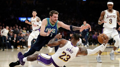 <p>               Los Angeles Lakers' LeBron James (23) recovers a loose ball under Dallas Mavericks' Luka Doncic (77) during the first half of an NBA basketball game Sunday, Dec. 1, 2019, in Los Angeles. (AP Photo/Marcio Jose Sanchez)             </p>