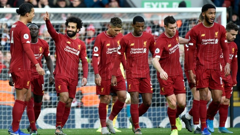 <p>               Liverpool's Mohamed Salah, 3rd left, celebrates with teammates after scoring his sides first goal during the English Premier League soccer match between Liverpool and Watford at Anfield stadium in Liverpool, England, Saturday, Dec. 14, 2019. (AP Photo/Rui Vieira)             </p>