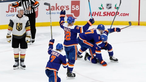 <p>               New York Islanders left wing Anders Lee (27) tackles defenseman Ryan Pulock (6), who scored in overtime of an NHL hockey game against the Vegas Golden Knights, Thursday, Dec. 5, 2019, in Uniondale, N.Y. Islanders right wings Jordan Eberle (7) and Josh Bailey (12) celebrate with raised sticks. (AP Photo/Kathy Willens)             </p>