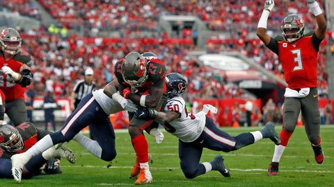 <p>               Tampa Bay Buccaneers running back Ronald Jones II (27) slips between Houston Texans inside linebacker Zach Cunningham (41) and linebacker Tyrell Adams (50) for a score during the first half of an NFL football game Saturday, Dec. 21, 2019, in Tampa, Fla. Quarterback Jameis Winston (3) celebrates the play. (AP Photo/Mark LoMoglio)             </p>