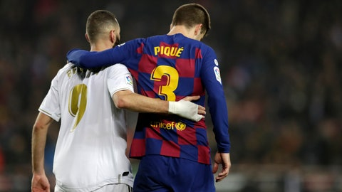 """<p>               Real Madrid's Karim Benzema, left, and Barcelona's Gerard Pique walks together on the pitch during a Spanish La Liga soccer match between Barcelona and Real Madrid at Camp Nou stadium in Barcelona, Spain, Wednesday, Dec. 18, 2019. Thousands of Catalan separatists are planning to protest around and inside Barcelona's Camp Nou Stadium during Wednesday's """"Clasico"""". (AP Photo/Bernat Armangue)             </p>"""
