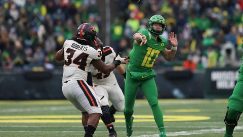 <p>               Oregon quarterback Justin Herbert (10) throws a pass away from Oregon State inside linebacker Avery Roberts (34) and defensive lineman Simon Sandberg (45) during the second half of an NCAA college football game in Eugene, Ore., Saturday, Nov. 30, 2019. (AP Photo/Amanda Loman)             </p>