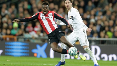 <p>               Athletic Bilbao's Inaki Williams, left, and Real Madrid's Sergio Ramos fight for the ball during a Spanish La Liga soccer match between Real Madrid and Athletic Bilbao at the Santiago Bernabeu stadium in Madrid, Spain, Sunday Dec. 22, 2019. (AP Photo/Paul White)             </p>