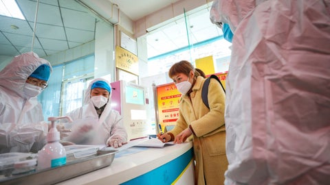<p>               Medical workers in protective gear talk with a woman suspected of being ill with a coronavirus at a community health station in Wuhan in central China's Hubei Province, Monday, Jan. 27, 2020. China on Monday expanded sweeping efforts to contain a viral disease by extending the Lunar New Year holiday to keep the public at home and avoid spreading infection. (Chinatopix via AP)             </p>