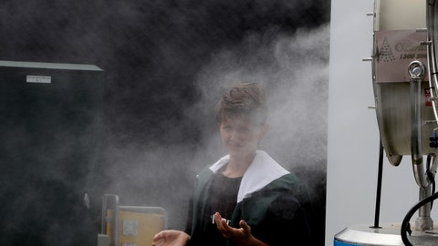 <p>               A spectator cools down in a front of a fan spraying water as qualifying matches continue ahead of the Australian Open tennis championship in Melbourne, Australia, Friday, Jan. 17, 2020. The season's opening Grand Slam event begins here Monday Jan. 20. (AP Photo/Mark Baker)             </p>