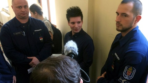 <p>               FILE - In this Tuesday, March 5, 2019 file photo, Portuguese Rui Pinto, center, is surrounded by police officers in the hallway of the Metropolitan Court in Budapest, Hungary, as he awaits a decision on his extradition to Portugal. Pinto denies wrongdoing. A Portuguese judge ruled Friday Jan. 17, 2020, that prosecutors have enough evidence incriminating Rui Pinto, an alleged hacker charged with publishing internal documents, to stand trial. (AP Photo/Pablo Gorondi, File)             </p>