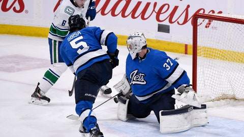 <p>               Winnipeg Jets goaltender Connor Hellebuyck (37) makes a save on Vancouver Canucks' Brock Boeser (6) as Luca Sbisa (5) defends during the third period of an NHL hockey game Tuesday, Jan. 14, 2020, in Winnipeg, Manitoba. (Fred Greenslade/The Canadian Press via AP)             </p>