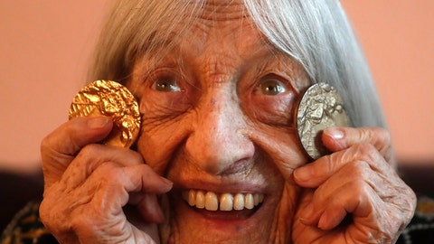 <p>               Agnes Keleti, former Olympic gold medal winning gymnast, poses for a photo with two of her Olympic medals at her apartment in Budapest, Hungary Wednesday Jan. 8, 2020. Although she turned 99 on Thursday, even a 9-year-old would have a hard time keeping up with Agnes Keleti's irrepressible energy and enthusiasm. Keleti is the oldest living Olympic champion and a Holocaust survivor. She won 10 medals in gymnastics — including five golds — at the 1952 Helsinki Games and at the 1956 Melbourne Games. (AP Photo/Laszlo Balogh)             </p>