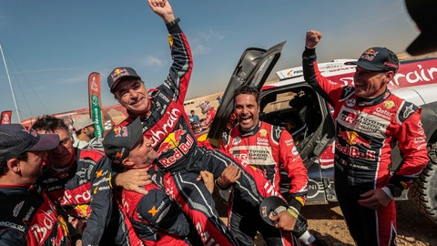 <p>               Driver Carlos Sainz, of Spain, center, is lifted by Driver StÈphane Peterhansel, of France, center and left, and driver Nasser Al-Attiyah, of Qatar, center and right, at the end of stage twelve of the Dakar Rally between Haradth and Qiddiya, Saudi Arabia, Friday, Jan. 17, 2020. (AP Photo/Bernat Armangue)             </p>