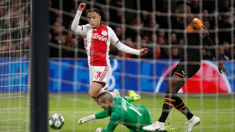 <p>               Valencia's goalkeeper Jaume Domenech saves on a shot by Ajax's Sergino Dest, center, during the group H Champions League soccer match between Ajax and Valencia at the Johan Cruyff ArenA in Amsterdam, Netherlands, Tuesday, Dec. 10, 2019. (AP Photo/Peter Dejong)             </p>