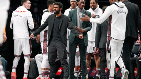 <p>               Injured Brooklyn Nets guard Kyrie Irving, center left, who has a right shoulder injury, reacts on the sideline with Caris LeVert, center right, who is also injured, during the first half of an NBA basketball game against the New York Knicks, Thursday, Dec. 26, 2019, in New York. (AP Photo/Kathy Willens)             </p>