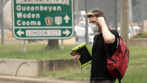 <p>               A pedestrian wears a mask as smoke shrouds the Australian capital of Canberra, Australia, Thursday, Jan. 2, 2020. Australia deployed military ships and aircraft to help communities ravaged by apocalyptic wildfires that destroyed homes and sent thousands of residents and holidaymakers fleeing to the shoreline. (AP Photo/Mark Baker)             </p>