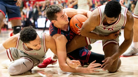 <p>               Dayton forward Ryan Mikesell, center, fights for the ball with Saint Joseph's forward Lorenzo Edwards, left, and guard Rahmir Moore, right, during the first half of an NCAA college basketball game, Sunday, Jan. 5, 2020, in Philadelphia. (AP Photo/Laurence Kesterson)             </p>