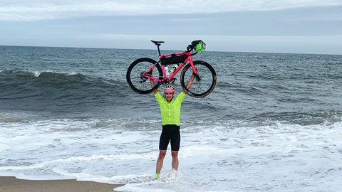 """<p>               This Oct. 7, 2019, photo provided by Jay Kolsch shows Rob Lea after finishing a cross country bike ride in Nantucket, R.I. Lea dubbed his trek """"The Ultimate World Triathlon"""" as he climbed Mount Everest through whipping wind, swam in the frigid waters of the English Channel wearing nothing more than a Speedo _ enduring constant jellyfish stings as well _ and rode his bike, through painful saddle sores, from one American coast to the other. (Jay Kolsch via AP)             </p>"""