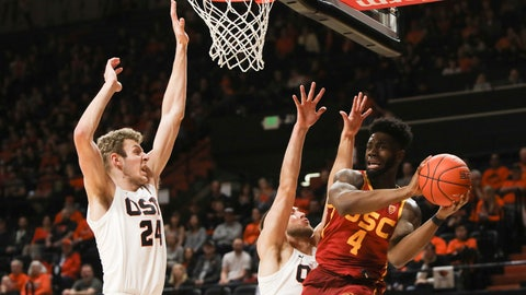 <p>               Southern California's Daniel Utomi (4) passes away from the basket to avoid Oregon State's Kylor Kelley (24) and Tres Tinkle (3) during the first half of an NCAA college basketball game in Corvallis, Ore., Saturday, Jan. 25, 2020. (AP Photo/Amanda Loman)             </p>