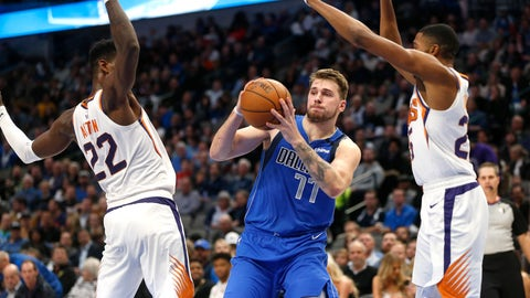 <p>               Dallas Mavericks guard Luka Doncic (77) looks to pass as Phoenix Suns center Deandre Ayton (22) and Phoenix Suns forward Mikal Bridges (25) defend during the second half of an NBA basketball game Tuesday, Jan. 28, 2020, in Dallas. Phoenix won 133-104. (AP Photo/Ron Jenkins)             </p>