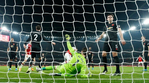 <p>               Manchester United goalkeeper David de Gea, center, lies on the ground after being beaten by Arsenal's Sokratis Papastathopoulos during the English Premier League soccer match between Arsenal and Manchester United at the Emirates Stadium in London, Wednesday, Jan. 1, 2020. (AP Photo/Matt Dunham)             </p>