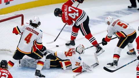 <p>               Chicago Blackhawks' John Quenneville (47) is unable to get a shot on goal as Calgary Flames' Rasmus Andersson (4), Cam Talbot (39) and Mark Giordano (5) defend during the third period of an NHL hockey game Tuesday, Jan. 7, 2020, in Chicago. The Flames won 2-1. (AP Photo/Charles Rex Arbogast)             </p>