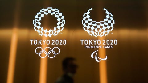 """<p>               FILE - In this June 11, 2019, file photo, a man walks past the Tokyo 2020 Olympic logos in Tokyo. One of the creative directors for this year's Tokyo Olympics has resigned following allegations of what are being termed """"power harassment."""" Kaoru Sugano stepped away from the position and his resignation has been confirmed by the Tokyo organizing committee. (AP Photo/Jae C. Hong, File)             </p>"""