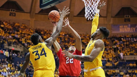 <p>               Texas Tech forward TJ Holyfield (22) goes to shoot as he is defended by West Virginia forwards Oscar Tshiebwe (34) and Derek Culver (1) during the first half of an NCAA college basketball game Saturday, Jan. 11, 2020, in Morgantown, W.Va. (AP Photo/Kathleen Batten)             </p>