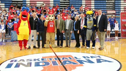 Dignitaries pose behind the Basketball Day Indiana logo at center court of historic Memorial Gymnasium at Kokomo High School, which will host the fourth annual event.