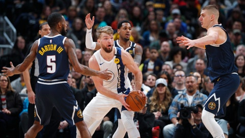 Indiana Pacers forward Domantas Sabonis, center, looks to pass the ball as, from left, Denver Nuggets guards Will Barton and Monte Morris and center Nikola Jokic defend in the second half of an NBA basketball game Sunday, Jan. 19, 2020, in Denver. Indiana won 115-107. (AP Photo/David Zalubowski)