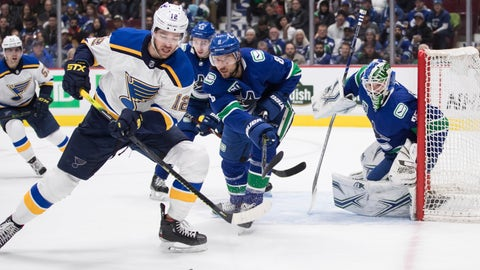 St. Louis Blues' Zach Sanford (12) reaches for the puck while being watched by Vancouver Canucks' Chris Tanev (8) in front of goalie Thatcher Demko (35) during the first period of an NHL hockey game in Vancouver, British Columbia on Monday Jan. 27, 2020. (Darryl Dyck/The Canadian Press via AP)