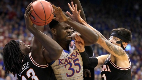 <p>               Kansas center Udoka Azubuike (35) rebounds between Oklahoma State guards Isaac Likekele (13) and Lindy Waters III (21) during the first half of an NCAA college basketball game in Lawrence, Kan., Monday, Feb. 24, 2020. (AP Photo/Orlin Wagner)             </p>