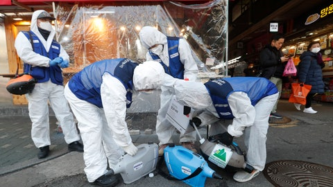 "<p>               Workers wearing protective gears prepare to spray disinfectant as a precaution against the coronavirus at a market in Seoul, South Korea, Monday, Feb. 24, 2020. South Korean President Moon Jae-in said his government had increased its anti-virus alert level by one notch to ""Red,"" the highest level. It allows for the temporary closure of schools and reduced operation of public transportation and flights to and from South Korea.  (AP Photo/Ahn Young-joon)             </p>"