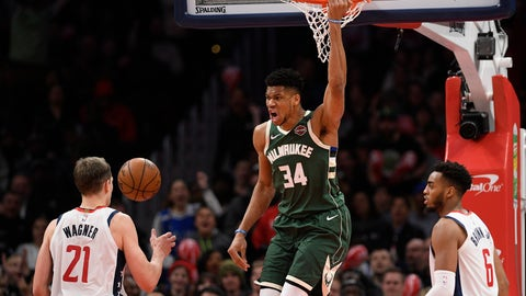 <p>               Milwaukee Bucks forward Giannis Antetokounmpo (34) hangs from the rim after his dunk during the second half of an NBA basketball game next to Washington Wizards forward Moritz Wagner (21) and forward Troy Brown Jr. (6) , Monday, Feb. 24, 2020, in Washington. (AP Photo/Nick Wass)             </p>