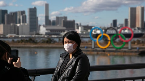 <p>               FILE - In this Jan. 29, 2020, file photo, a tourist wearing a mask poses for a photo with the Olympic rings in the background, at Tokyo's Odaiba district. Tokyo Olympic organizers repeated their message at the start of two days of meetings with the IOC: this summer's games will not be cancelled or postponed by the coronavirus spreading  neighboring China. (AP Photo/Jae C. Hong, File)             </p>