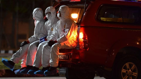 <p>               In this photo taken and released by Malaysia's Ministry of Health, health workers wearing full protective suits sit on a vehicle as they wait for the arrival of evacuated Malaysian from China's Wuhan, the epicenter of the coronavirus outbreak, at Kuala Lumpur International Airport in Sepang, Malaysia, Wednesday, Feb. 26, 2020. U.S. health officials warned Tuesday that the burgeoning coronavirus is certain to spread more widely in the country at some point, even as their counterparts in Europe and Asia scrambled to contain new outbreaks of the illness. (Muzzafar Kasim/Malaysia's Ministry of Health via AP)             </p>
