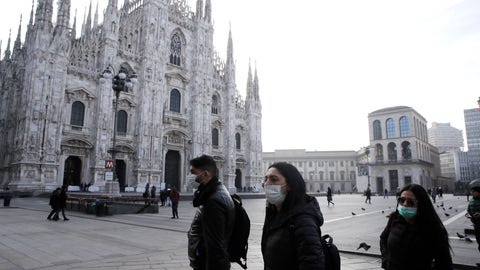 <p>               People wearing sanitary masks walk past the Duomo gothic cathedral in Milan, Italy, Sunday, Feb. 23, 2020. A dozen Italian towns saw daily life disrupted after the deaths of two people infected with the virus from China and a pair of case clusters without direct links to the outbreak abroad. A rapid spike in infections prompted authorities in the northern Lombardy and Veneto regions to close schools, businesses and restaurants and to cancel sporting events and Masses. (AP Photo/Luca Bruno)             </p>